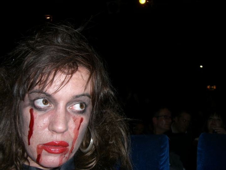 Foreground: hideous corpse. Background: serious cinemagoers